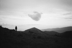 image en noir et blanc : une montage, une silhouette et un nuage