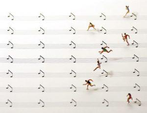 art miniature : des personnages font une course de haies sur une partition de musique