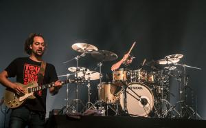 sur scène, une batterie et un homme qui joue de la guitare